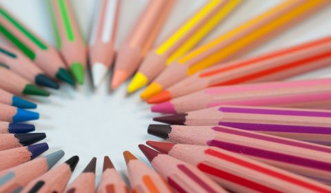 Colourful pencils all pointing towards the centre of a circle