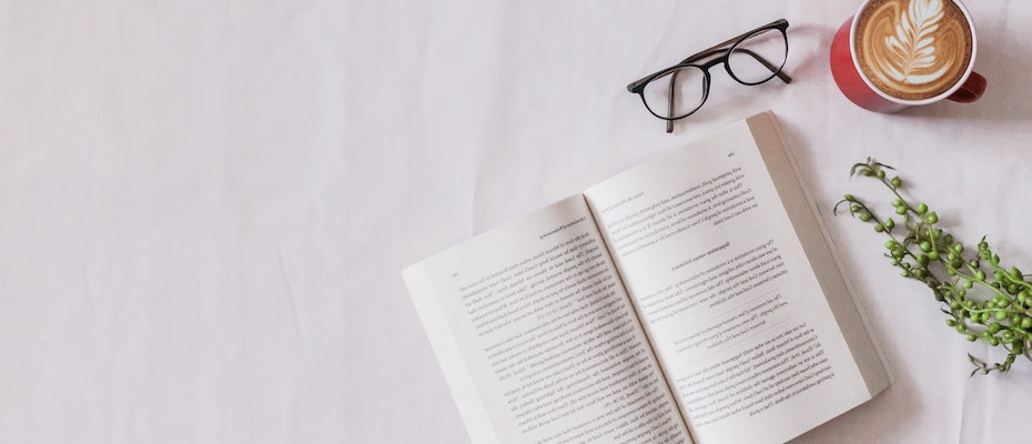 Book, glasses, coffee and a plant