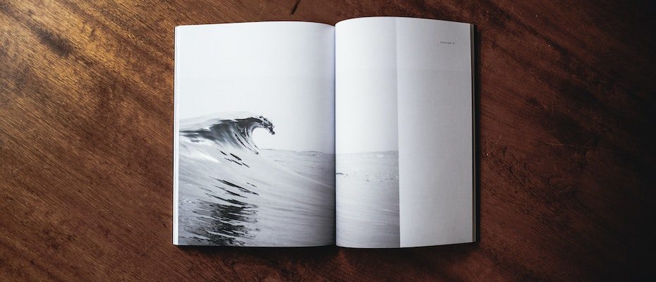 Open book with the image of a cresting wave